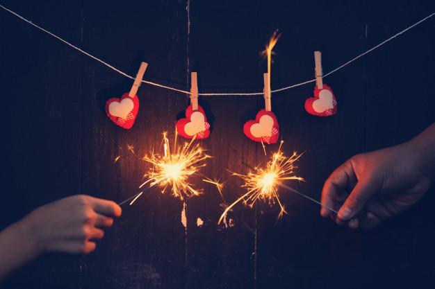 Paar die brandende sterretjes met valentijnskaart achtergrondconcept  houden.   Premium Foto